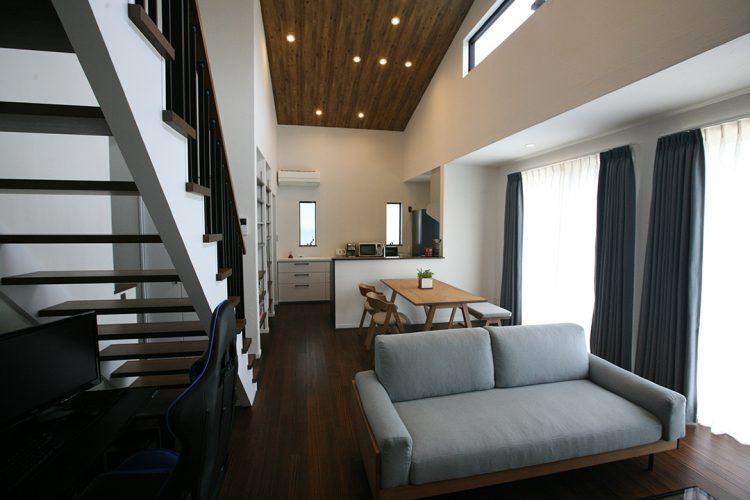 ゼロエネルギー住宅のLDK、吹き抜け天井は木目調のクロス貼り仕上げ
