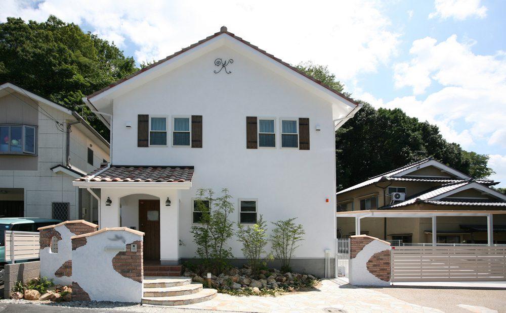 真っ白な塗り壁と土焼きの瓦屋根、かわいい外観。